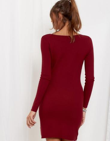 Modelka ubrana w bordową obcisłą sukienkę