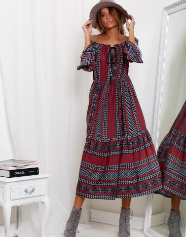 Modelka w kapeluszu ubrana w długą modną sukienkę