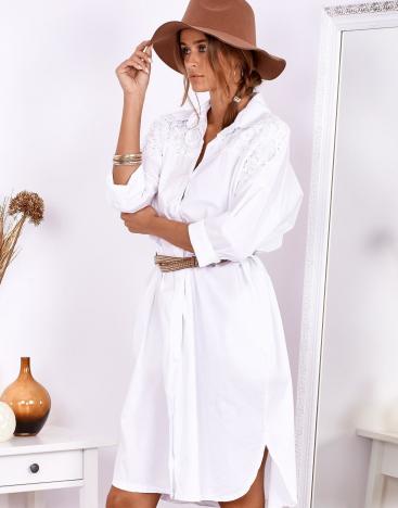 Modelka w kapeluszu, ubrana w białą letnią sukienkę